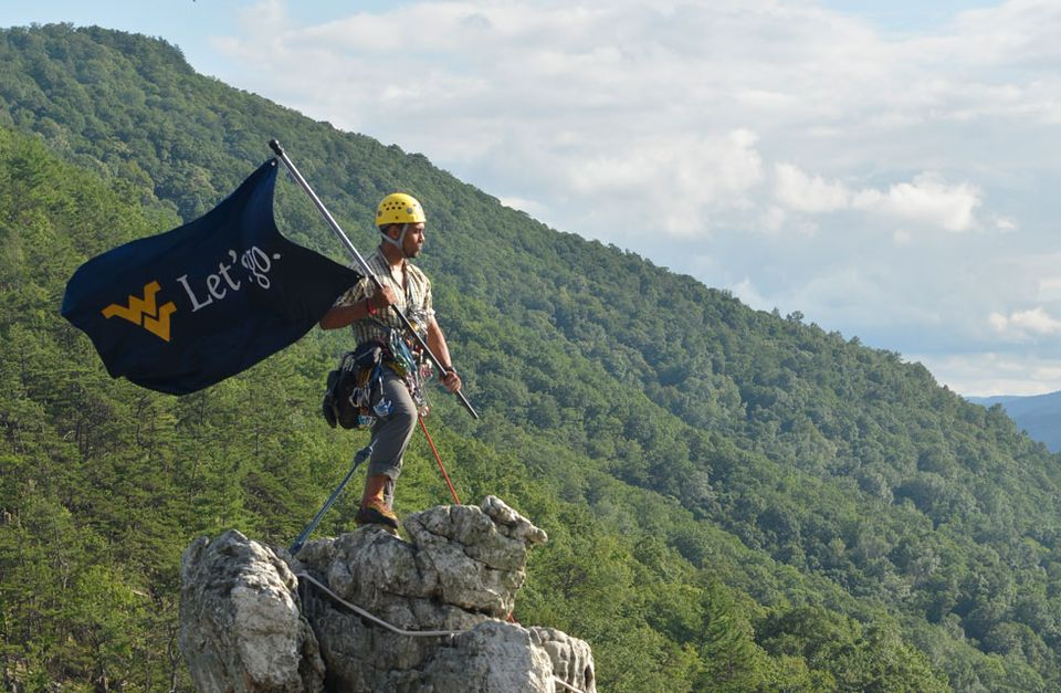 "A man on top of a mountain holding a flag with the flying WV that says ""Let's Go""."