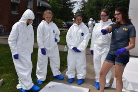 Forensics camp members in crime scene gear, listening to instructor
