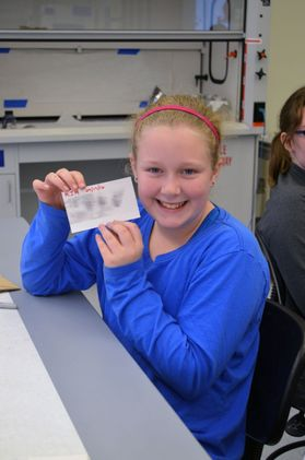 School child holds up fingerprinting card.