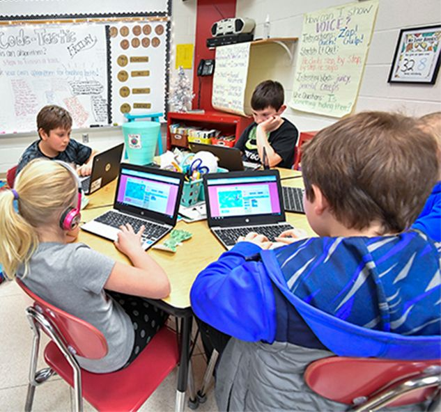 Elementary students in a classroom working on Hour of Code activities on laptops