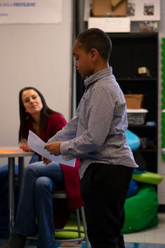 Lorenze looks on as a student reads from a script