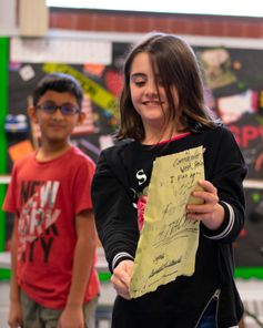 A girl and a boy present a piece of paper to the class in the classroom