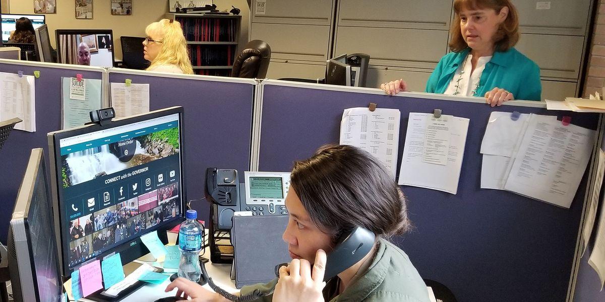 Coronavirus hotline with people answering phones.