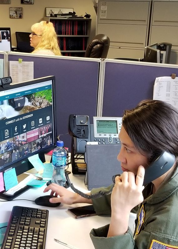 Photo of woman answering phone at coronavirus hotline.