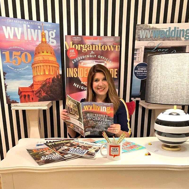 Nikki Bowman holding a WV Living magazine in her office.