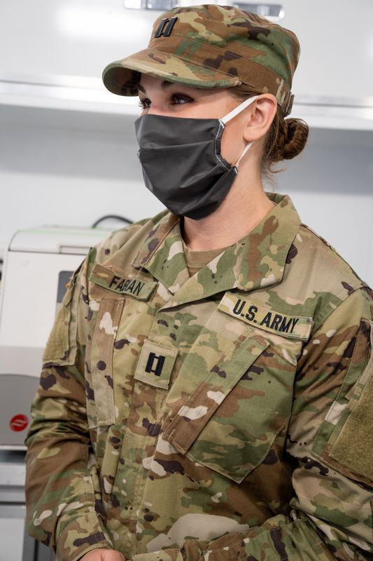 Photo of Samantha Fabian in National Guard fatigues and a face mask.