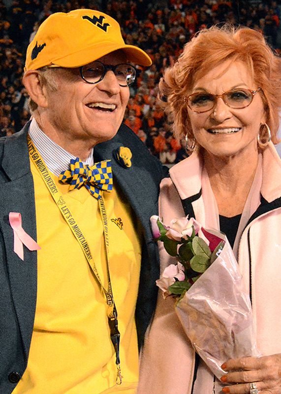 Gordon Gee with his arm around Betty Puskar who is holding roses. They are at a football game.
