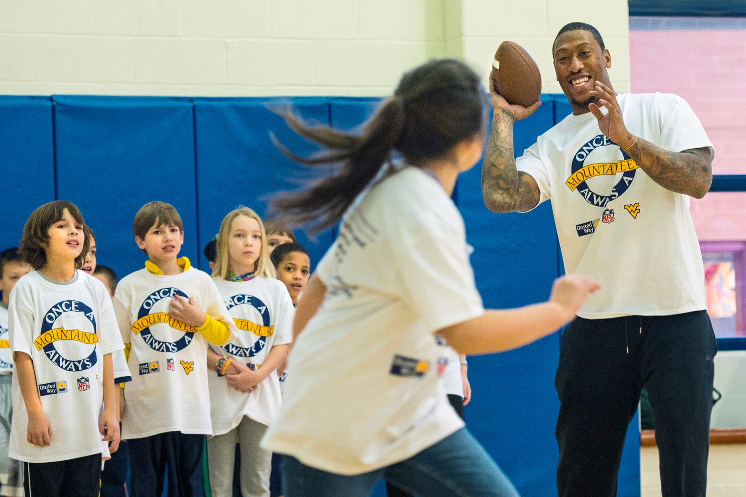 Bruce Irvin plays football with children.