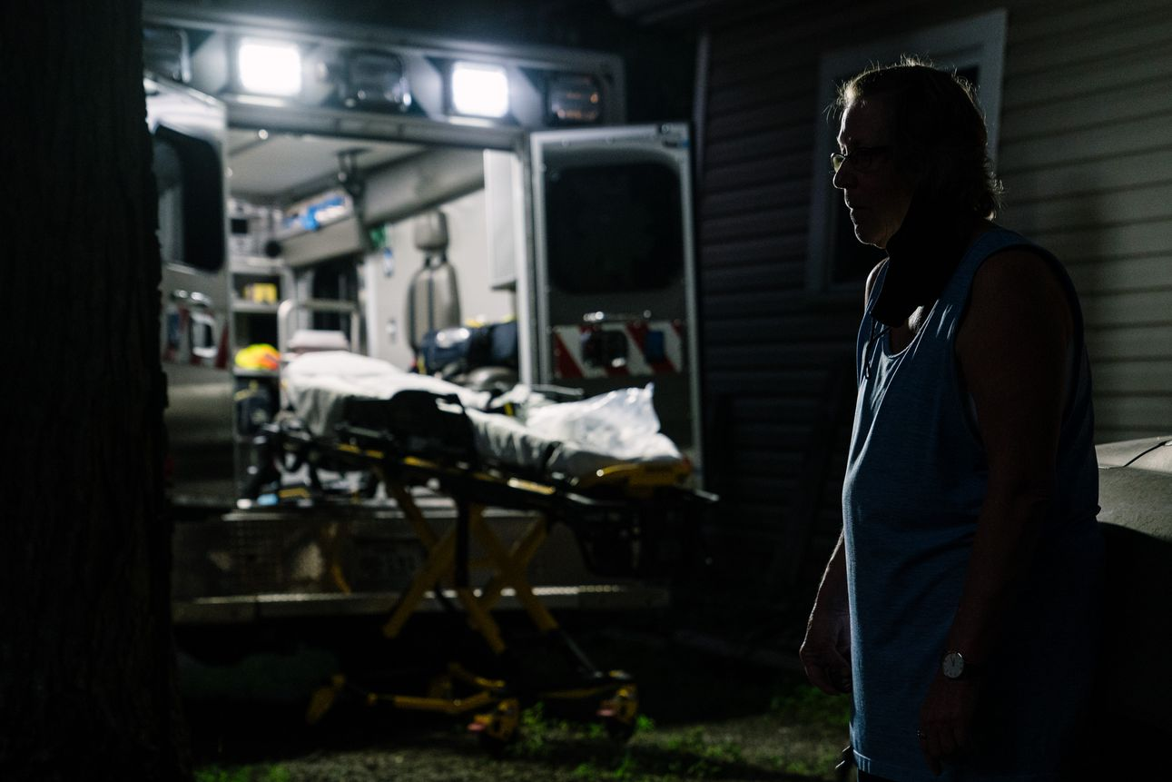 The relative of a deceased man believed to have been infected with COVID-19 stands near the ambulance waiting to take her relative to a local funeral home on August 6th, 2020.