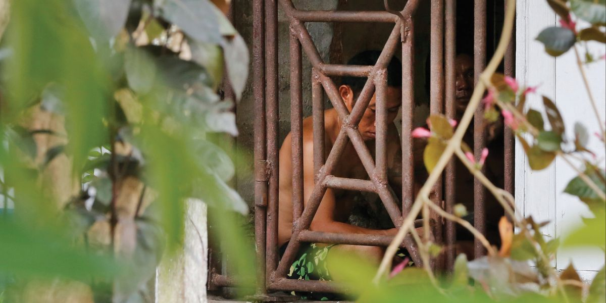 Enslaved man inside a cage in Indonesia.