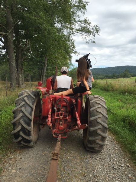 Elaine McMillions rides with her camera on a tractor.