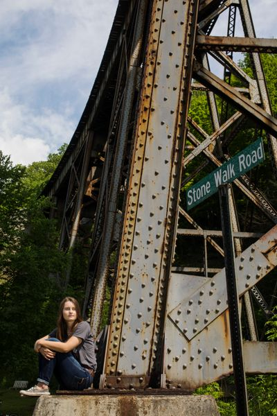 Savannah Lusks sits beside a train trestle.