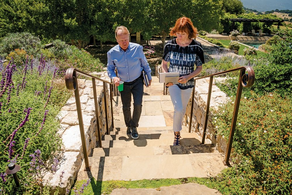 John Chambers walks with assistant