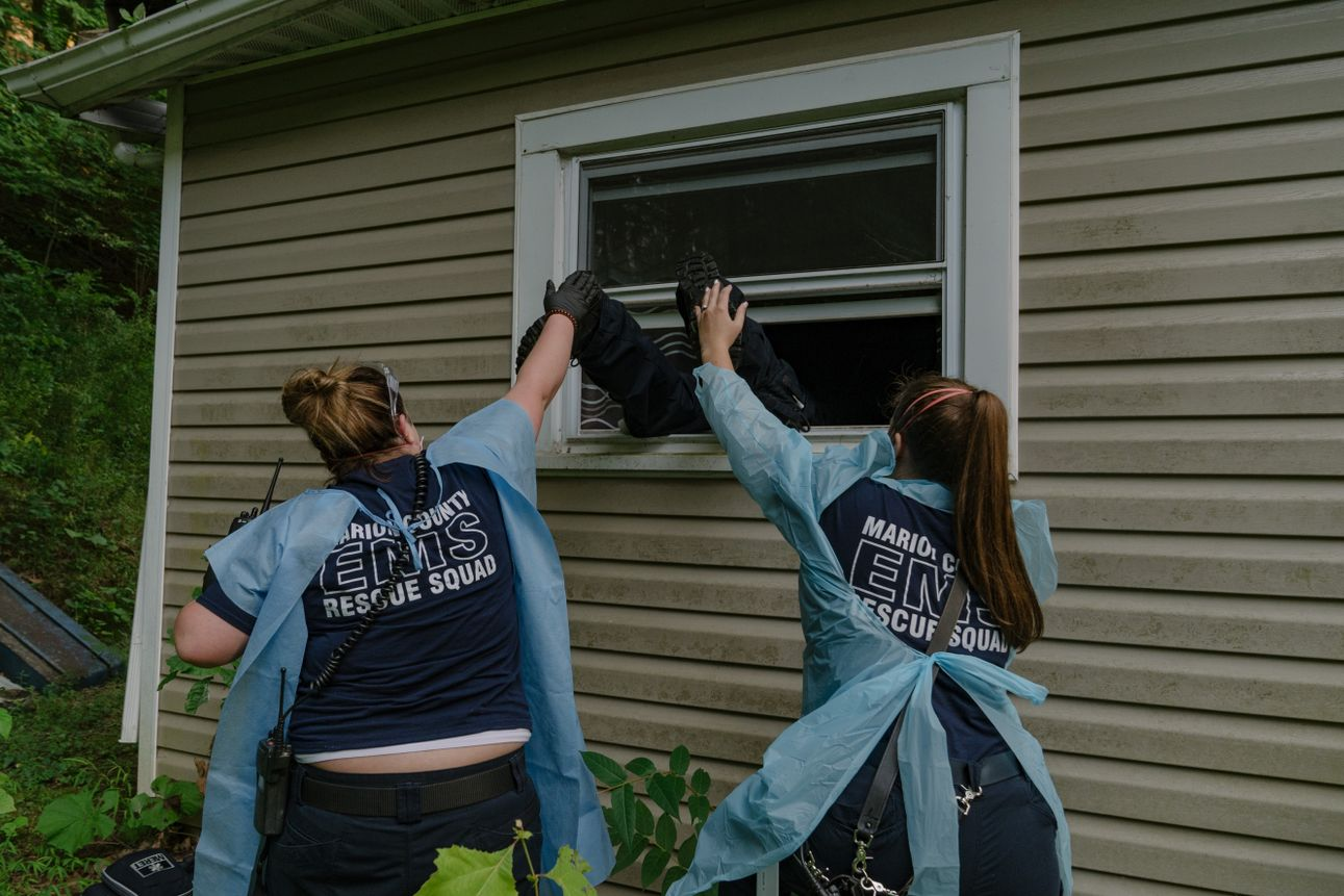 Marion County EMS medics push one of their coworkers into the window of a residence after discovering the front door was locked in Marion County, West Virginia. The patient was presumed to have COVID-19, requiring extra PPE on August 6th, 2020.