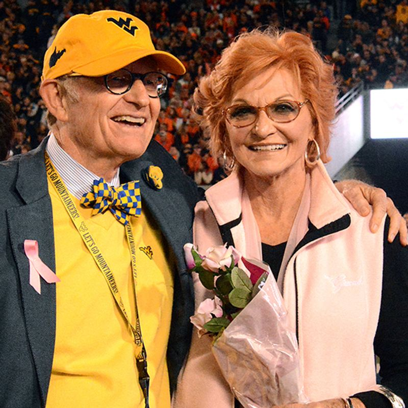 Gordon Gee with his arm around Betty Puskar, who is holding roses. They are at a football game.
