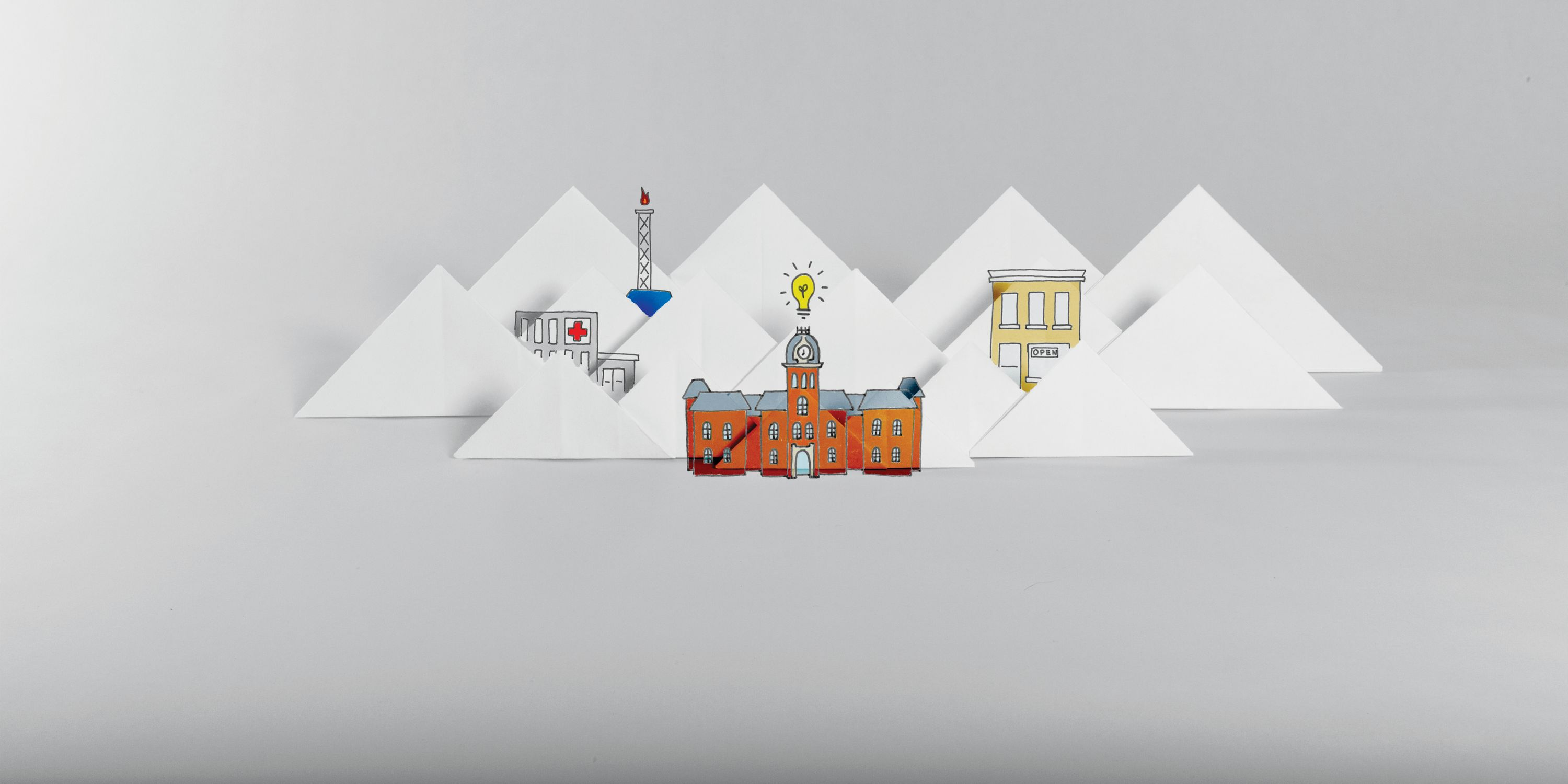 Origami depiction of Woodburn Hall, a gas well and a downtown among mountains