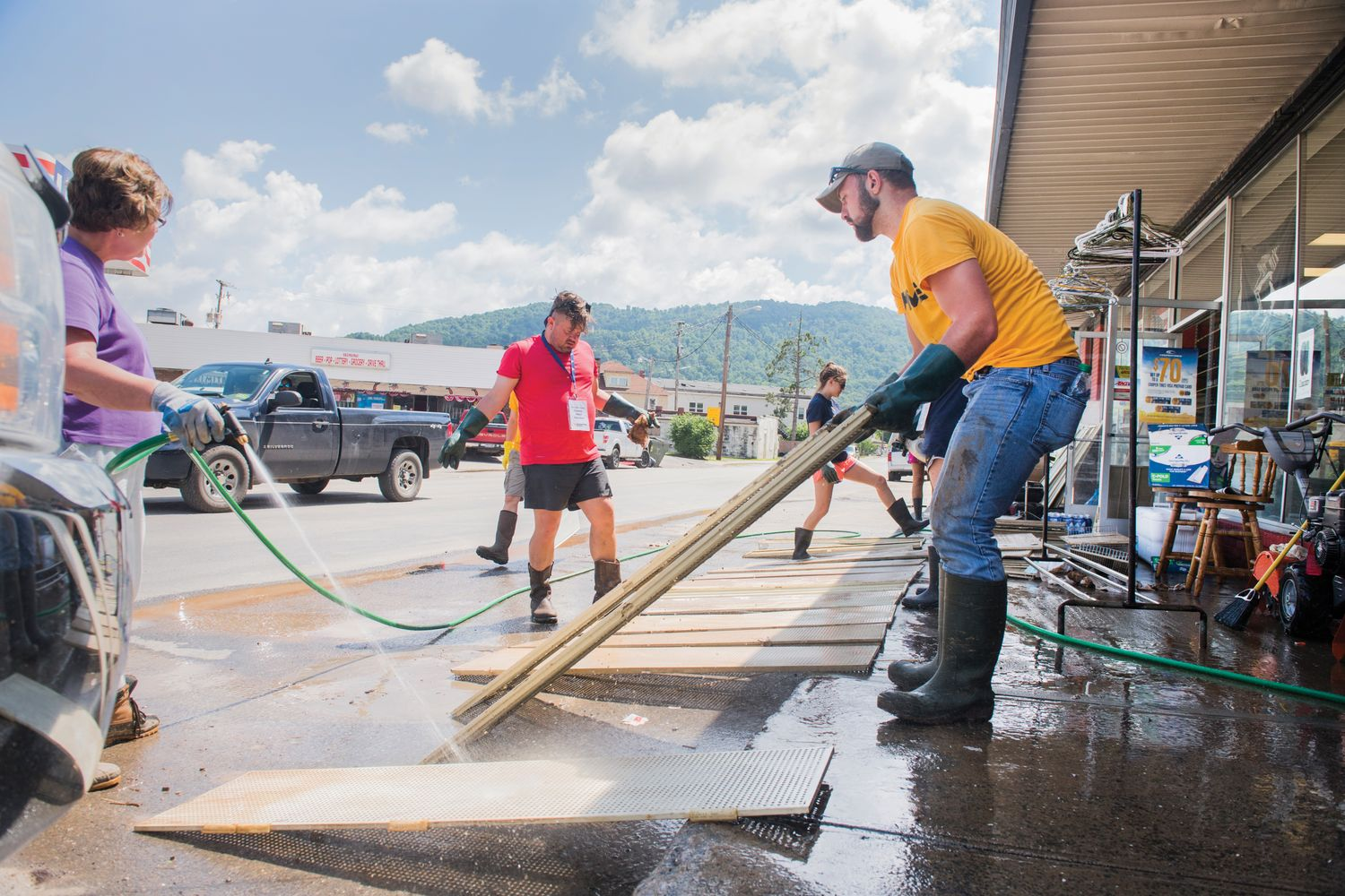 Volunteers help a store owner clean up after the flood.