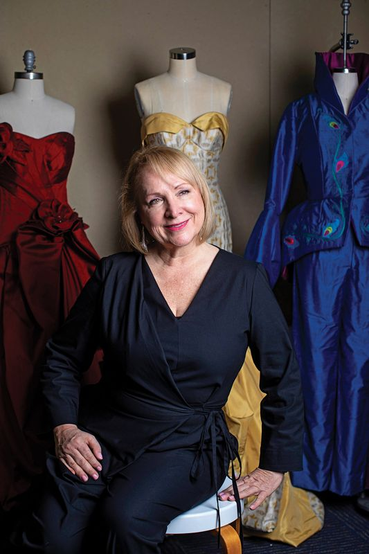 Colleen Moretz with dresses in background.