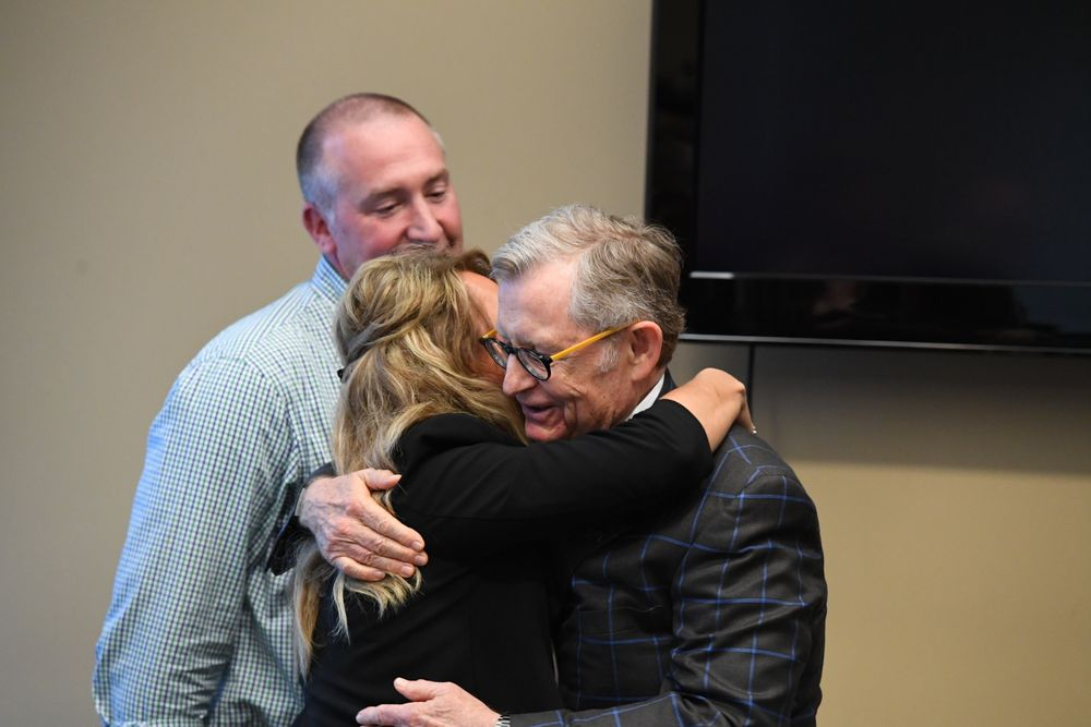 President Gee embraces Kim Burch while her husband TJ looks on.