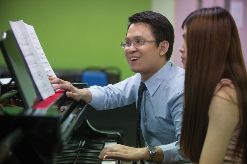 Yew Choong Cheong works with a student at the piano.