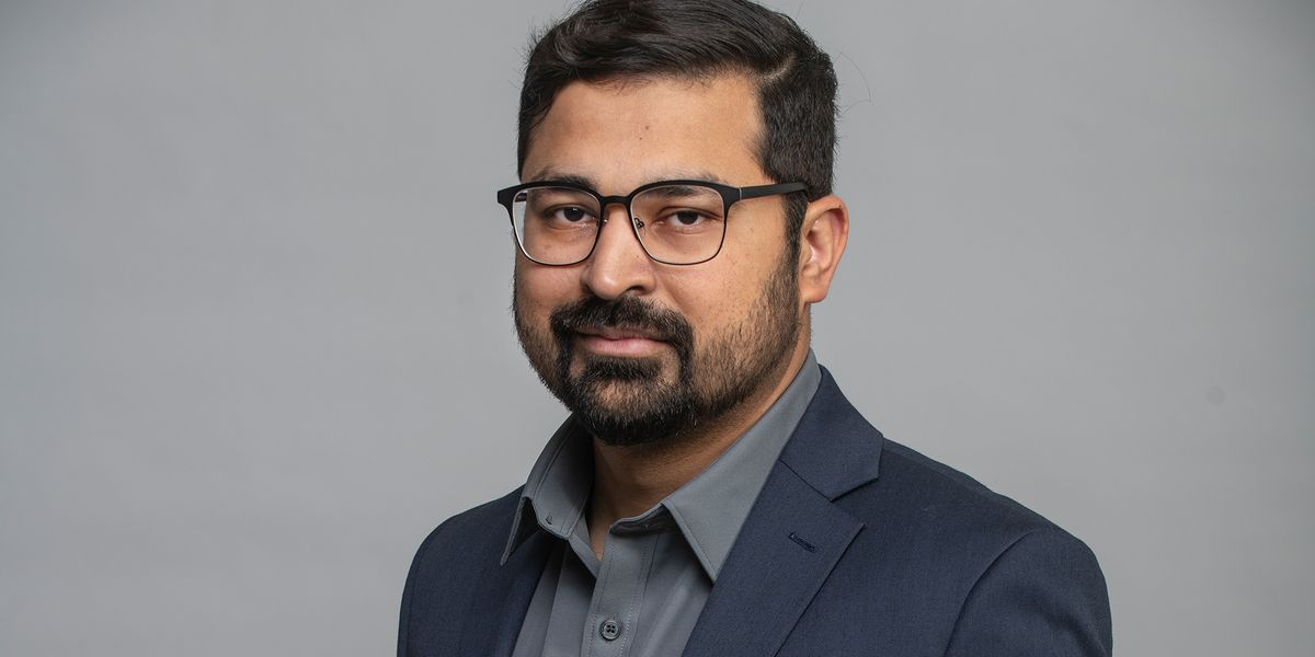 Portrait of Safi Khan against a gray backdrop.