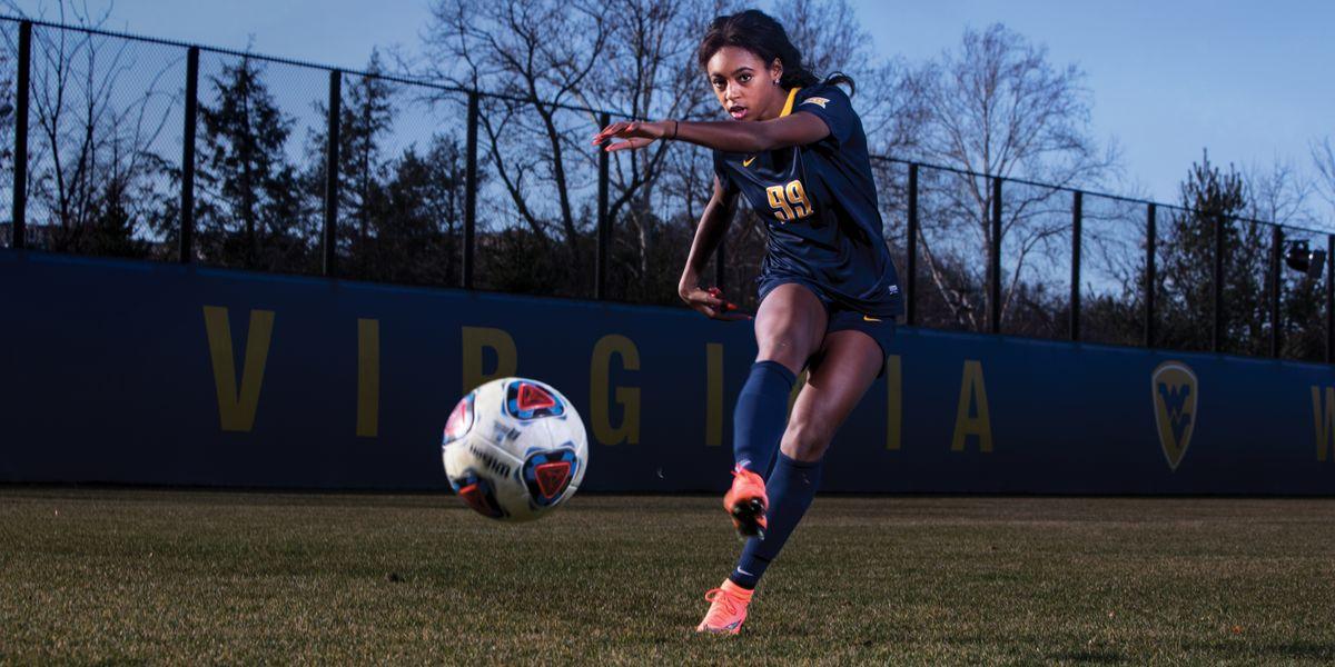 Soccer player kicking ball toward the viewer.