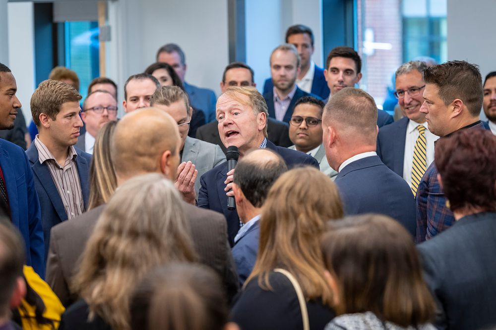 John Chambers speaking in a crowd.