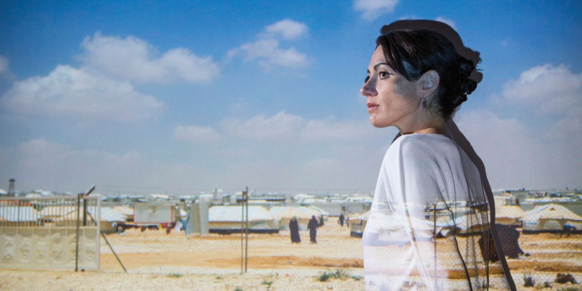 Karen Culcasi stands in front of a photo she took of a refugee camp in Jordan.