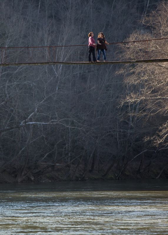 Photo of women standing on a bridge spanning a river.  The Rocky Branch Bridge crosses the South Fork of the Kentucky River and connects communities to the outside world in the event of flooding. March 9, 2017 By Nancy Andrews