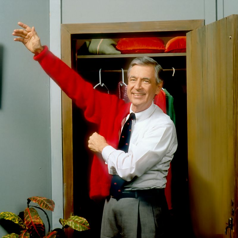 Mister Rogers putting on sweater photo