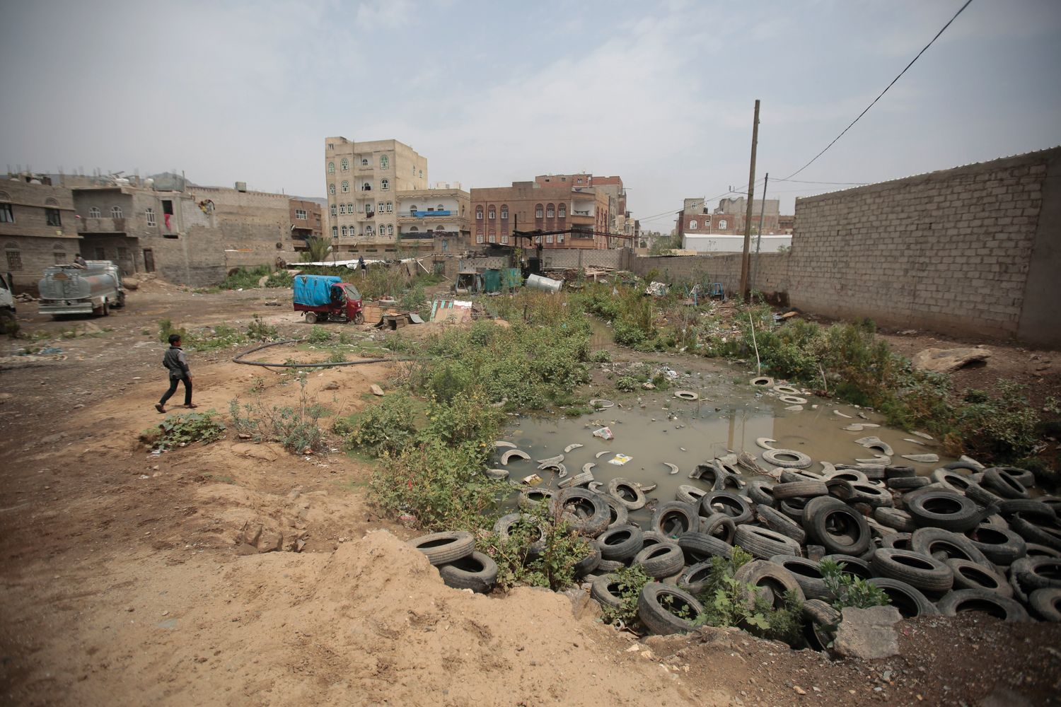 A boy walks beside a sewage swamp in Yemen.