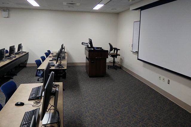 tables, chairs, computers, instructor podium, and screen.