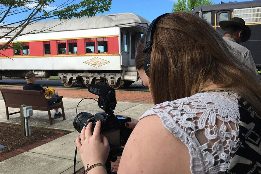 A WVU Reed College of Media student takes photos at a train station during the 2018 project.