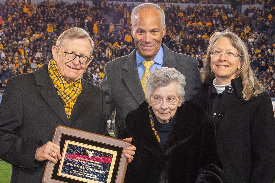 WVU President E. Gordon Gee presents the Most Loyal West Virginian award to Loulie Canady in 2018. College of Creative Arts Dean Keith Jackson and Kathy DeGraff stand behind her.