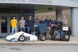 The Mountaineer Racing Powertrain team Team pose with the 2017 Formula SAE race car and the engine dynamometer built with funds donated by DENSO North America Foundation