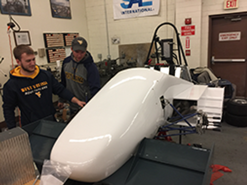Ian Smithson and Logan Horn admire car 87's new bodywork manufactured with the generous support of Aurora Flight Science of Bridgeport WV.