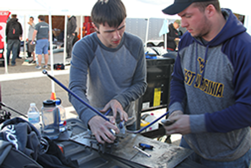 Skyler Comstock and Logan Horn work to repair a suspension failure at the 2017 Formula SAE® Michigan Competition.