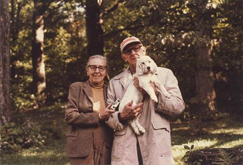 Photograph of George and Kay Evans with their little white dog named Holly in 1980.