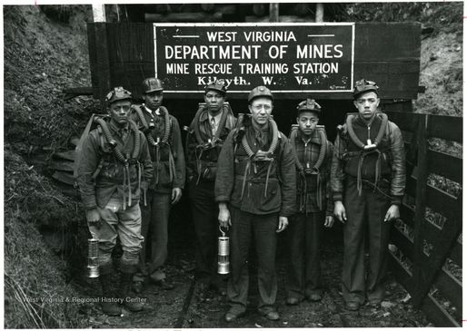 A black-and-white photograph of miners in front of a WV Department of Mines sign