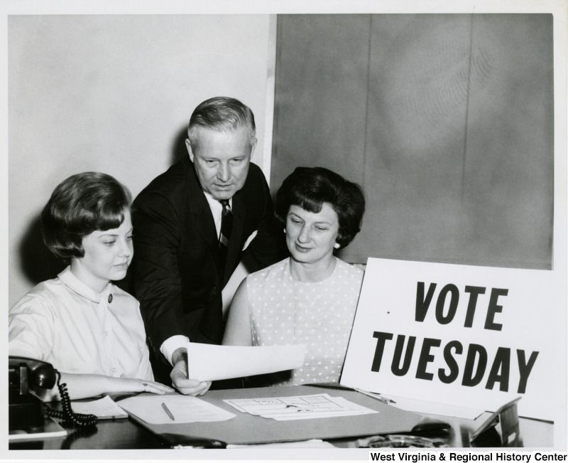 "Black-and-white photograph of Arch Moore with Shelley Moore and a girl sitting next to a sign that says ""Vote Tuesday"""