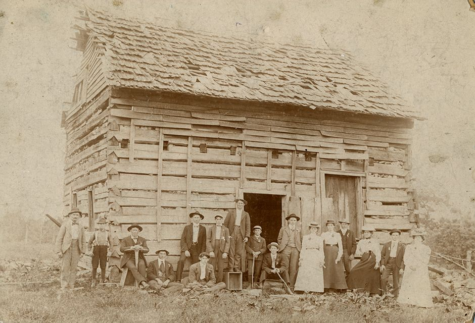 Group of people in front of log cabin.