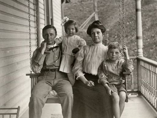 A black-and-white photograph of a family of four on a porch swing