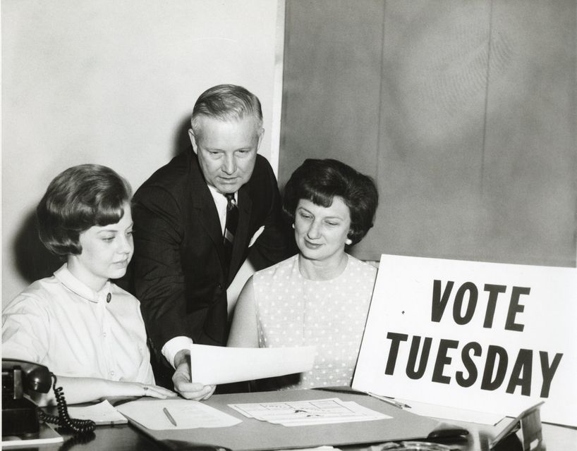 "Black-and-white photograph of Arch Moore and Shelley Moore behind a ""Vote Tuesday"" sign"