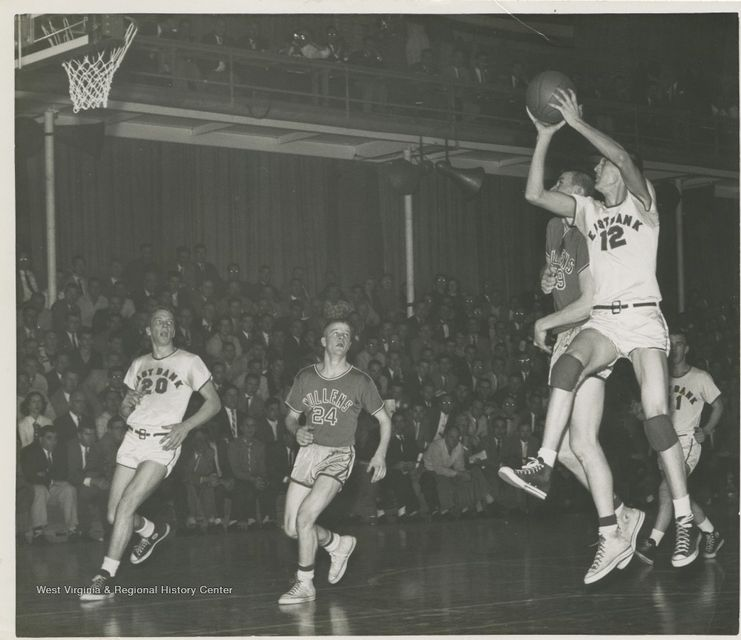 Photograph of Jerry West shooting a basketball with four other players near him.