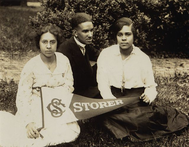 Photograph of three Storer College students holding a Storer pennant