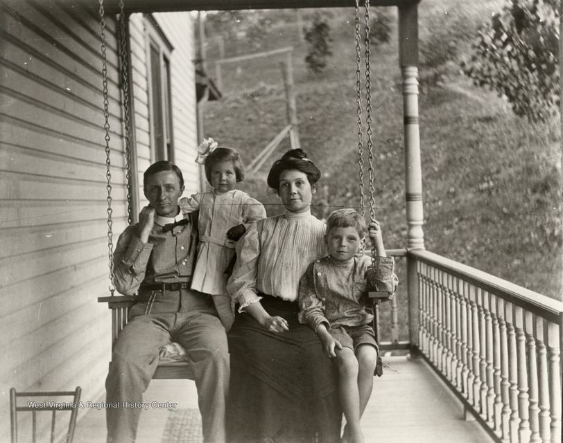 Black-and-white photograph of a man, woman, and two children on a porch swing.