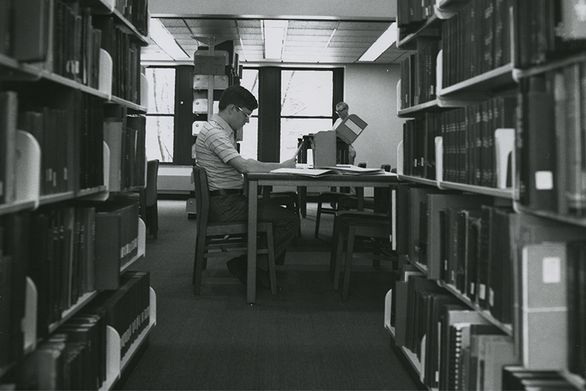 Man looking through archival box in library.