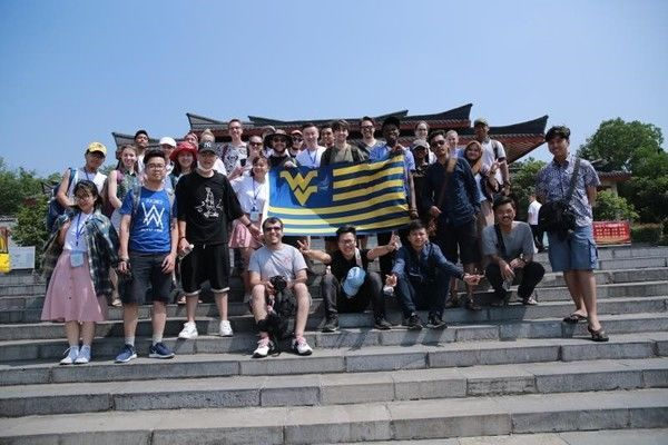 Picture of international students in China with WVU flag