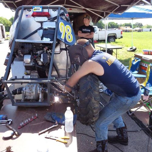 WVU makes repairs to the rear suspension in the Pitts at the 2017 Baja SAE Competition.