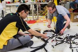 Students working on a vehicle wiring harness